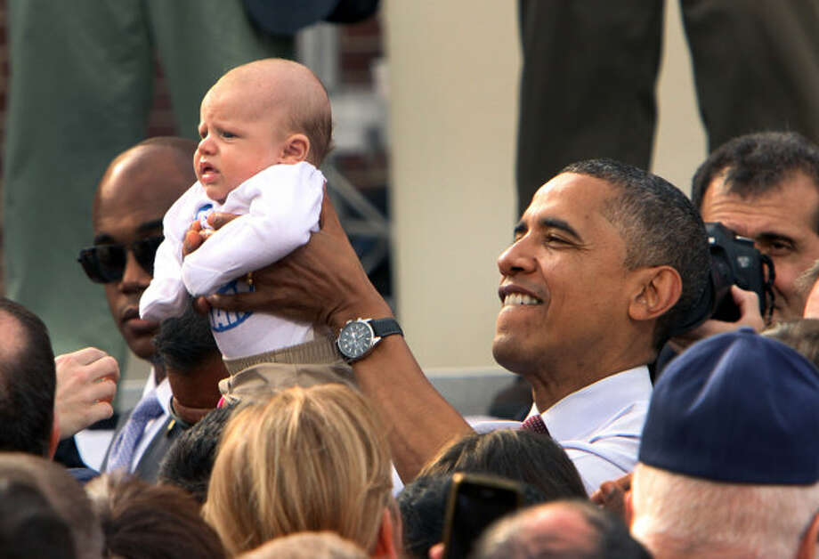 President Barack Obama holds up a baby at a campaign event at Elm Street Middle School, Saturday, Oct. 27, 2012 in Nashua, N.H.  (Jim Cole / AP Photo)