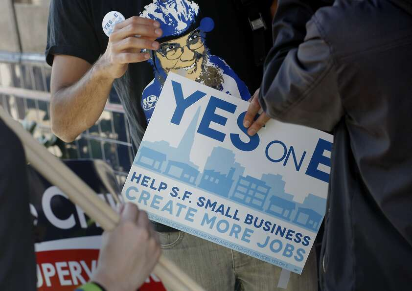 Backers hand out posters supporting the Proposition E business tax measure, which passed.