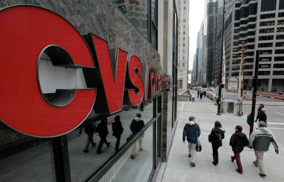 FILE- In this Feb 7, 2012 file photo, pedestrians walk pass a CVS store in Chicago.  CVS Caremark Corp. said Tuesday, Nov. 6, 2012, that its third-quarter earnings climbed 16 percent. The drugstore operator and pharmacy benefits manager posted revenue increases in both businesses, benefiting from new customers won from rivals, and raised its full-year earnings outlook. (AP Photo/M. Spencer Green, File) Photo: M. Spencer Green