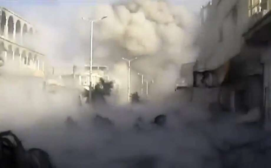 Smoke rises from an area of Houla, Syria, that was blasted by military aircraft. New battles between government and rebel forces killed more than 140 people. Photo: Anonymous, Associated Press