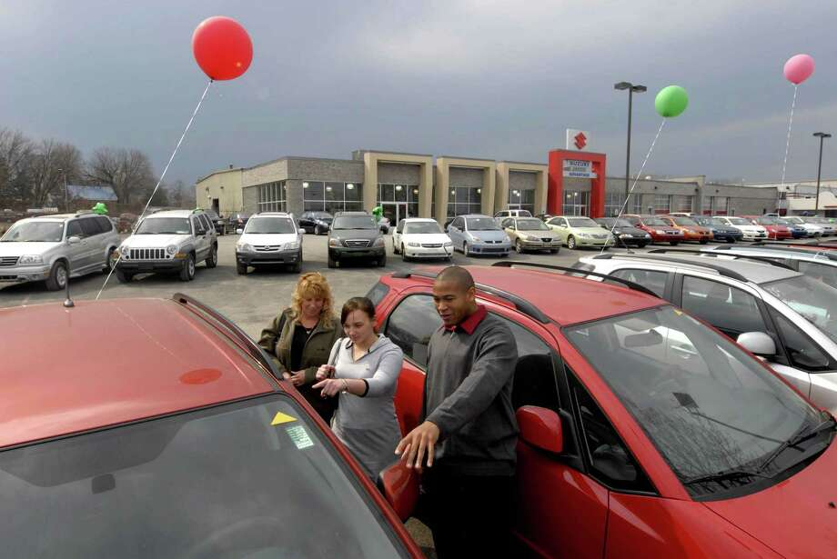 Car salesman Jamaal Crawford shows Elizabeth Chichester and her mother Vicky Braunsdorf  some of the vehicles at Advantage Suzuki in Albany, New York 3/18/2009. ( Michael P. Farrell / Times Union ) Photo: MICHAEL P. FARRELL / 00002976A