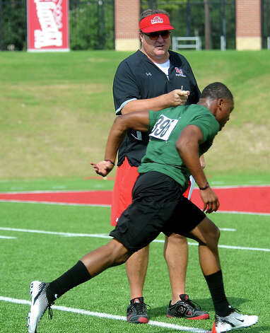 Lamar coach, Ray Woodard times a player as he runs trials during the Lamar Football Junior Senior camp at Provost Umphrey Stadium at Lamar University in Beaumont, Saturday, July 21, 2012. Tammy McKinley/The Enterprise Photo: TAMMY MCKINLEY