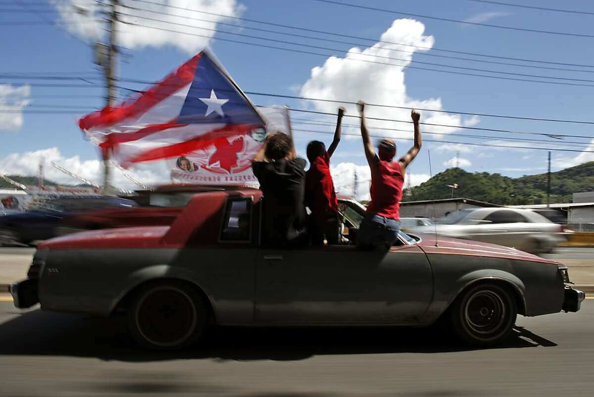 People ride atop a vehicle waving a Puerto Rican flag during elections in San Juan, Puerto Rico, Tuesday, Nov. 6, 2012. Puerto Ricans are electing a governor as the U.S. island territory does not get a vote in the U.S. presidential election. But they are also casting ballots in a referendum that asks voters if they want to change the relationship to the United States. A second question gives voters three alternatives: become the 51st U.S. state, independence, or sovereign free association, a designation that would give more autonomy.