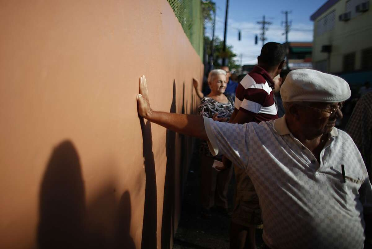 Voters wait in line to cast their ballots outside a polling station during elections in San Juan, Puerto Rico, Tuesday, Nov. 6, 2012. Puerto Ricans are electing a governor as the U.S. island territory does not get a vote in the U.S. presidential election. But they are also casting ballots in a referendum that asks voters if they want to change the relationship to the United States. A second question gives voters three alternatives: become the 51st U.S. state, independence, or sovereign free association, a designation that would give more autonomy.
