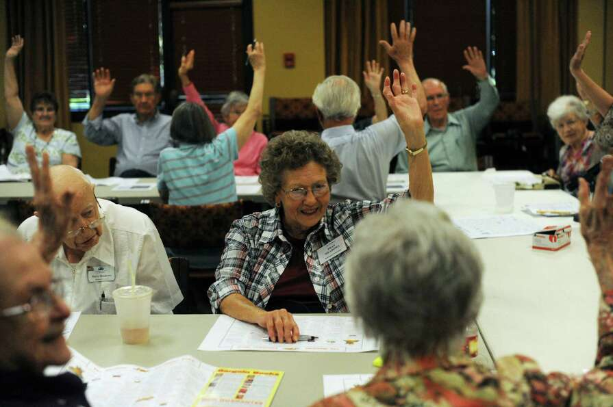 Senior citizens at Morngingside at The Meadows raise their hands during a meeting to signify that th
