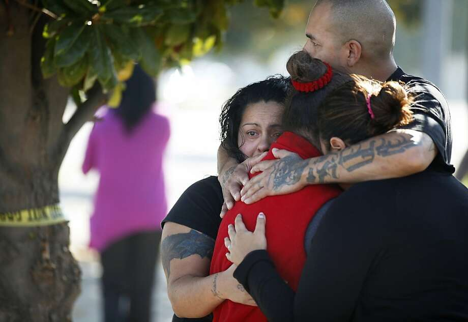 Onlookers hug outside the police perimeter near a chicken processing plant where a gunman killed two co-workers and then himself. Police said the gunman chose specific victims. Photo: Craig Kohlruss, Associated Press