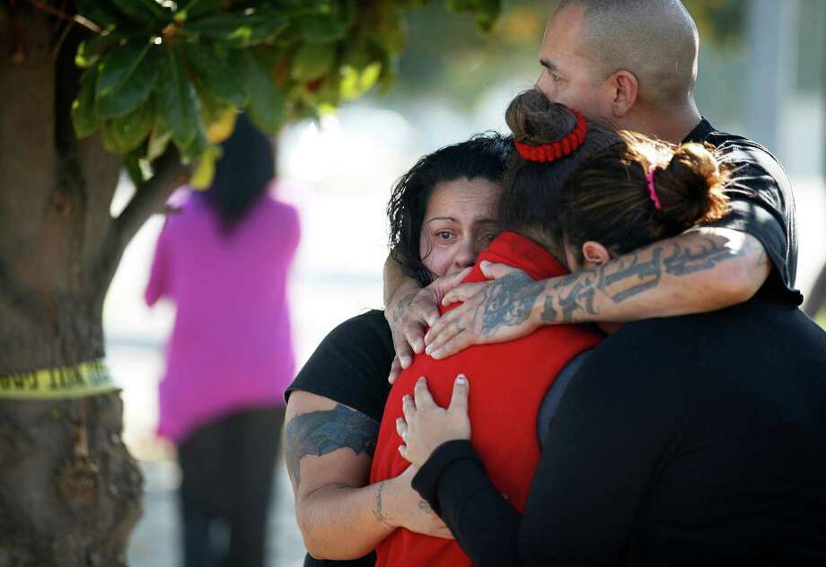 People embrace outside a chicken processing plant in Fresno, Calif., where a worker went on a shooting rampage. Photo: Craig Kohlruss, Associated Press / The Fresno Bee