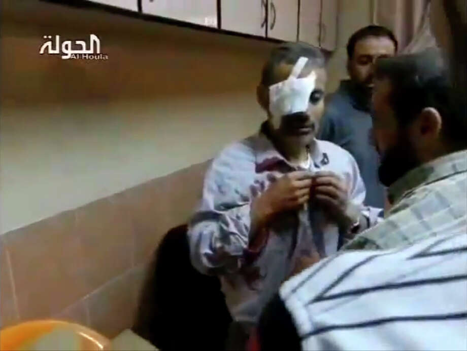 A video image shows a man at a hospital in Houla, Syria, who was wounded in a bombing by warplanes during air raids. Photo: Associated Press, Shaam News Network / Shaam News Network