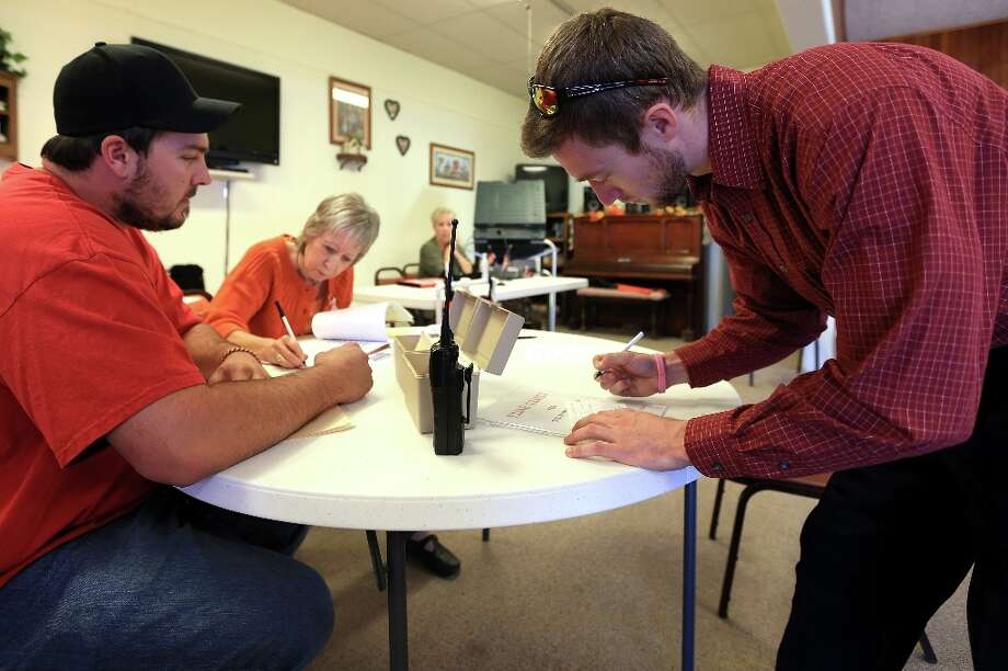 EADS, CO - NOVEMBER 06:  Voter Matt Smith (R) signs in with election judge Justin Crow (L) and volunteer Areta Blooding-Laird (C) in Kiowa County Precinct Two at the Eads Senior Citizens Center on November 6, 2012 in Eads, Colorado. Colorado is considered a swing state in the presidential race, with a prize of nine electoral votes.  (Photo by Doug Pensinger/Getty Images) Photo: Doug Pensinger, Getty Images / 2012 Getty Images