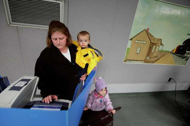 Bloomdale, OH  - NOVEMBER 6: Misty Schinsky votes while holding her son, Parker, 1, and daughter, Calley, 3, looking on, November 6, 2012 in Bloomdale, Ohio. Voting is underway in the US presidential election in the battleground state of Ohio. Recent polls show that U.S. President Barack Obama and Republican presidential candidate Mitt Romney are in a tight race. (Photo by J.D. Pooley/Getty Images) Photo: J.D. Pooley, Getty Images / 2012  Getty Images
