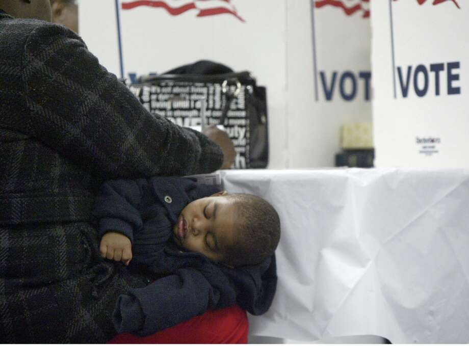 Man'Yari Vance, 1, naps on his grandmother, Angela Robertson's lap, as she casts her ballot at Hope Lighthouse Church on Election Day,  Tuesday, Nov.6, 2012, in Muskegon Heights, Mich. After a grinding presidential campaign President Barack Obama and Republican presidential candidate, former Massachusetts Gov. Mitt Romney, yield center stage to American voters Tuesday for an Election Day choice that will frame the contours of government and the nation for years to come. (AP Photo/The Muskegon Chronicle, Ken Stevens) ALL LOCAL TV OUT; LOCAL TV INTERNET OUT Photo: Ken Stevens, Associated Press / The Muskegon Chronicle