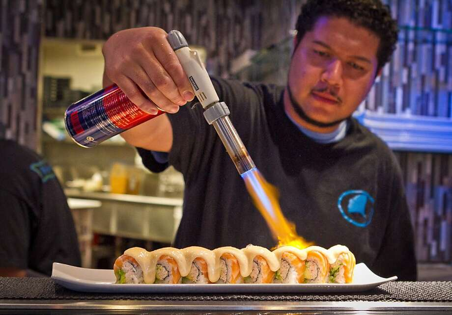 Chef Benjamin Stroughter fires the Salmon Melt sushi roll at Blue Gingko restaurant in Danville. Photo: John Storey, Special To The Chronicle