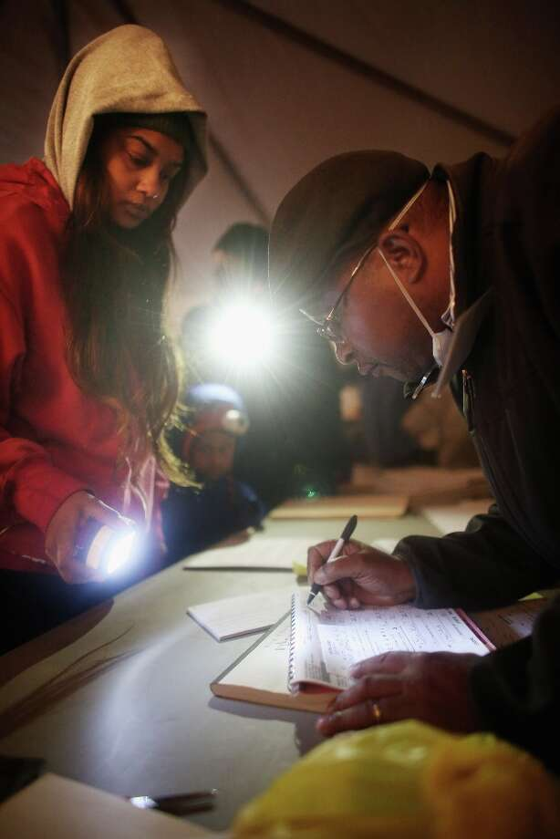 NEW YORK, NY - NOVEMBER 06: Rockaway resident Sheresa Walker (L) uses a flashlight as poll worker Lloyd Edwards assists before voting in a makeshift tent set up as a polling place at Scholars' Academy, PS 180, in the Rockaway neighborhood on November 6, 2012 in the Queens borough of New York City. The Rockaway section of Queens was one of the hardest hit areas. Many voters in New York and New Jersey are voting at alternate locations in the presidential election due to disruption from Superstorm Sandy.  (Photo by Mario Tama/Getty Images) Photo: Mario Tama, Getty Images / 2012 Getty Images