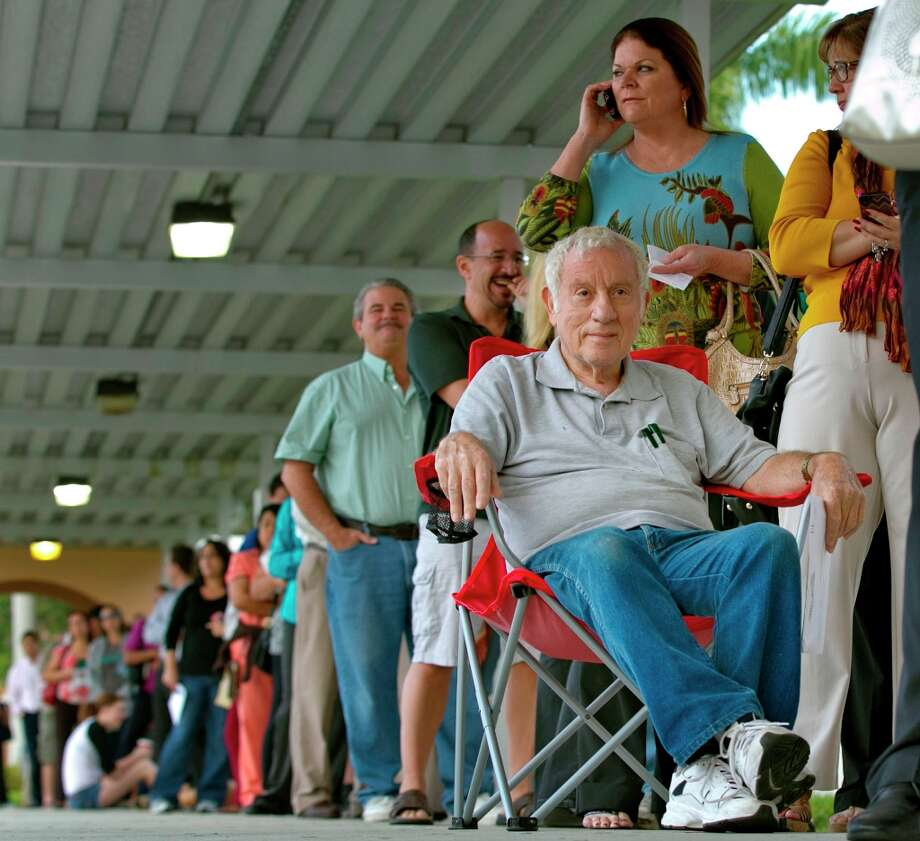 Matt Novick, of Southwest Ranches, sits in a chair while waiting in line to vote at the Southwest Regional Library in Pembroke Pines, Fla. on Election Day Tuesday, Nov. 6, 2012. (AP Photo/The Miami Herald, Joe Rimkus Jr.)  MAGS OUT Photo: Joe Rimkus Jr., Associated Press / The Miami Herald