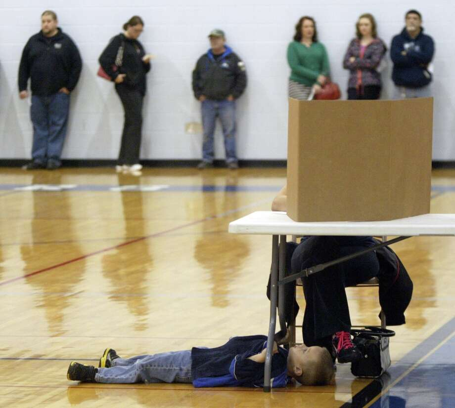 Avery Davis, 4, passes the time lying on his back as his mother, Samantha Davis, 30, votes in the the general election at the Mona Shores Middle School gym in Norton Shores, Mich., on Tuesday, Nov. 6, 2012.  They waited nearly an hour for Samantha to vote. (AP Photo/The Muskegon Chronicle, Ken Stevens) ALL LOCAL TV OUT; LOCAL TV INTERNET OUT Photo: Ken Stevens, Associated Press / The Muskegon Chronicle