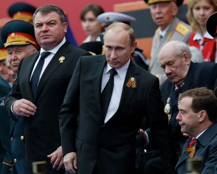 In this Wednesday, May 9, 2012 file photo, Russia's Defense Minister Anatoly Serdyukov, left, Russian President Vladimir Putin, center, and Prime Minister Dmitry Medvedev, bottom right, watch the Victory Day Parade, in Moscow. Russian President Vladimir Putin has fired the country's defense minister two weeks after a criminal probe was opened into alleged fraud in the sell-off of military assets. Putin made the announcement of Anatoly Serdyukov's dismissal on Tuesday Nov. 6, 2012 in a meeting with Moscow regional governor Sergei Shoigu, whom he appointed as the new minister. Photo: Alexander Zemlianichenko, Associated Press / AP