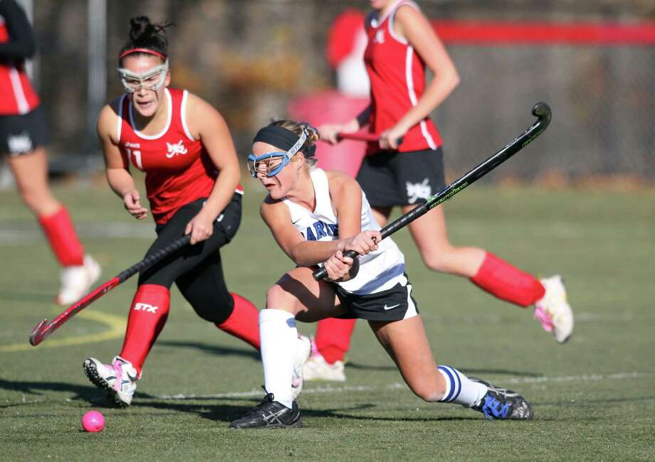 Darien High School player Kat Huber fires a backhanded shot on goal while New Canaan couterpart Michelle Halpert defends. The Blue Wave won their match easily, 3-0,to become co-owners of the FCIAC field hockey crown this season. © J. Gregory Raymond Photo: J. Gregory Raymond / Stamford Advocate Freelance;  © J. Gregory Raymond