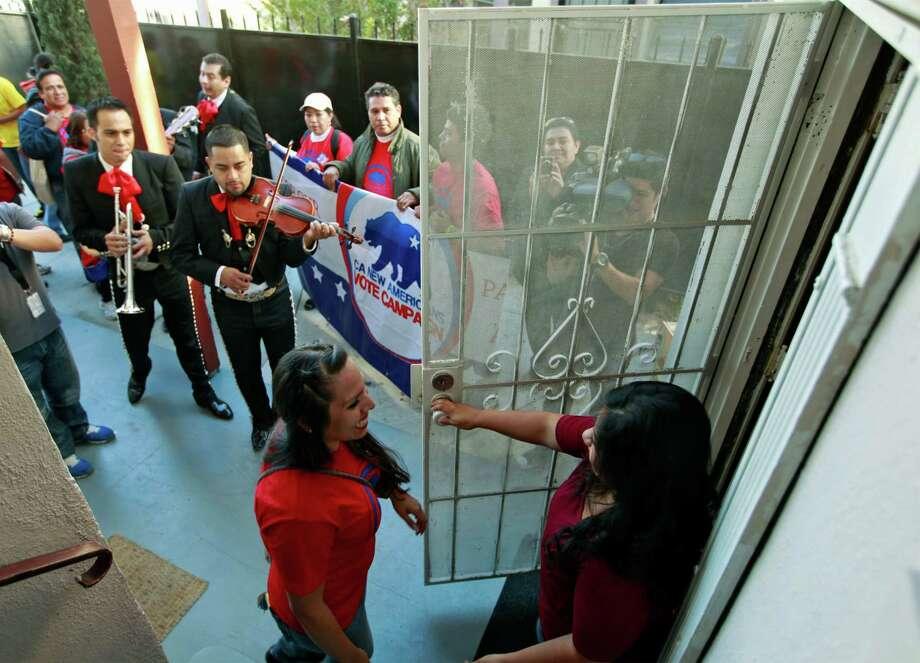 "Rosanna Del Rio, left, greets registered voter Edna Hernandez as the mariachi band ""Gallos de Jalisco"" serenades voters Tuesday, Nov. 6, 2012 in Los Angeles. (AP Photo/Damian Dovarganes) Photo: Damian Dovarganes, STF / AP"