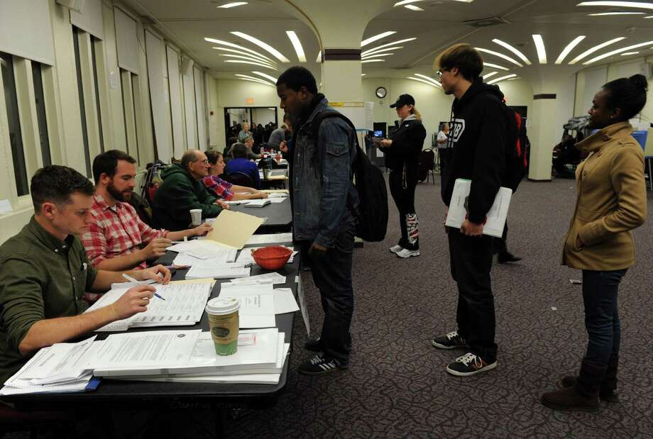 Voting inspectors Chris Scoville, left, and Harrison Watkins check in student voters at the University at Albany in Albany, NY Tuesday Nov. 6, 2012. (Michael P. Farrell/Times Union) Photo: Michael P. Farrell, Albany Times Union