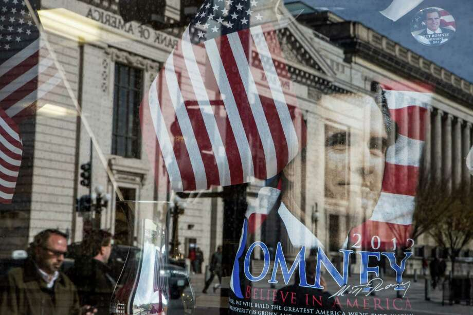 WASHINGTON, D.C. - NOVEMBER 6: A street scene is reflected in the window of a gift shop near the White House on November 6, 2012 in Washington, DC. As Americans go to vote, recent polls show that President Barack Obama and Republican presidential candidate former Massachusetts Gov. Mitt Romney are in a virtual tie in the national polls. (Photo by Brendan Hoffman/Getty Images)  *** BESTPIX *** Photo: Brendan Hoffman, Getty Images / 2012 Getty Images