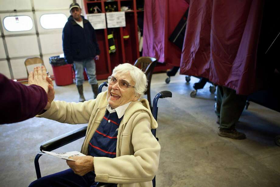 BAY HEAD, NJ - NOVEMBER 06:  Bety Etzel high-fives her daughter-in-law after voting in the presidential election in Bay Head Fire Station 14 on November 6, 2012 in Bay Head, New Jersey. As the New Jersey coastline continues to recover from Superstorm Sandy, numerous polling stations have had to be merged and relocated due to storm damage and power outages.  (Photo by Andrew Burton/Getty Images)  *** BESTPIX *** Photo: Andrew Burton, Getty Images / 2012 Getty Images