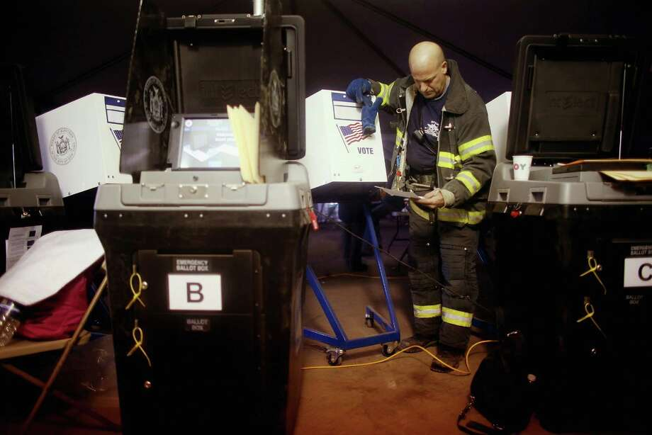 NEW YORK, NY - NOVEMBER 06:  Rockaway resident and New York City firefighter Terence O'Donnell stands on sand among voting machines as he prepares to vote in a makeshift tent set up as a polling place at Scholars' Academy, PS 180, in the Rockaway neighborhood on November 6, 2012 in the Queens borough of New York City. The Rockaway section of Queens was one of the hardest hit areas and O'Donnell's home is damaged. Many voters in New York and New Jersey are voting at alternate locations in the presidential election due to disruption from Superstorm Sandy.     (Photo by Mario Tama/Getty Images)  *** BESTPIX *** Photo: Mario Tama, Getty Images / 2012 Getty Images
