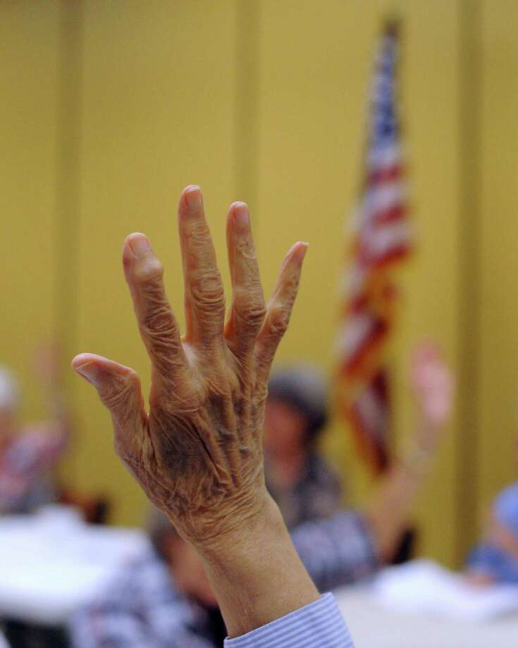 Senior citizens at Morngingside at The Meadows raise their hands during a meeting to signify that they voted in the 2012 election on Nov. 6, 2012. Photo: Billy Calzada, San Antonio Express-News / © 2012 San Antonio Express-News