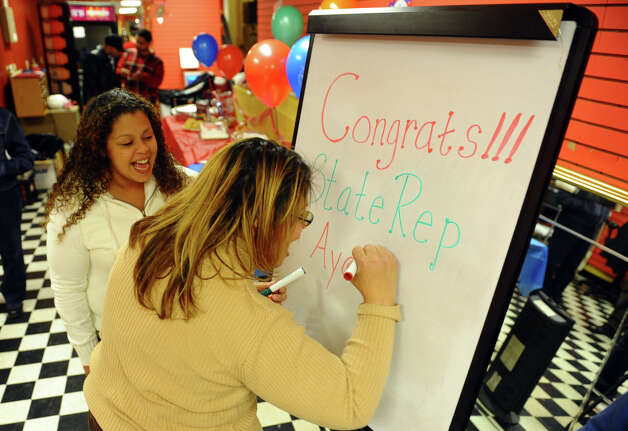 Campaign worker Aidee Nieves draws Christina Ayala's name on a board as Ayala's sister Lisa Quinones looks on at Ayala's headquarters on East Main Street in Bridgeport, Conn. on Tuesday November 6, 2012. Ayala is the expected democratic winner for the state representative seat in the 128th district. Photo: Christian Abraham / Connecticut Post