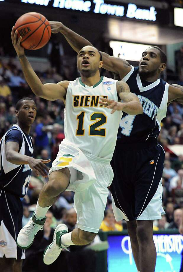 From left, Siena's Rakeem Brookins is defended by Saint Peter's Ryan Bacon as he goes up for a layup during a basketball game at the Times Union Center in Albany, NY on Wednesday, February 16, 2011.  (Lori Van Buren / Times Union) Photo: Lori Van Buren / 00011629F