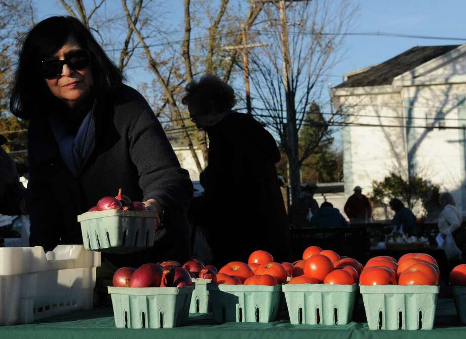 Mary Ann Donnaruma of Delmar picks out some onions from Hope Valley Farm of Hope Falls N.Y., at the First United Methodist Church Farmers Market on Kenwood Ave. in Delmar, N.Y. Tuesday afternoon Nov. 6, 2012. Will Waldron / Times Union) Photo: Ww