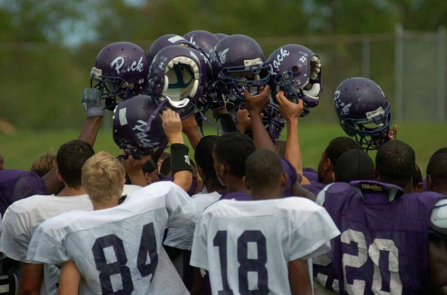 Lufkin High School football team raises their helmets after pratice, Friday, September 30, 2005, after a week where many players homes still didn't have power from hurricane Rita. The team is 3-0 in the season, and their game against Klein Forrest was last week was postponed due to weather. Johnny Hanson Chronicle Photo: Johnny Hanson, Contract / Contract