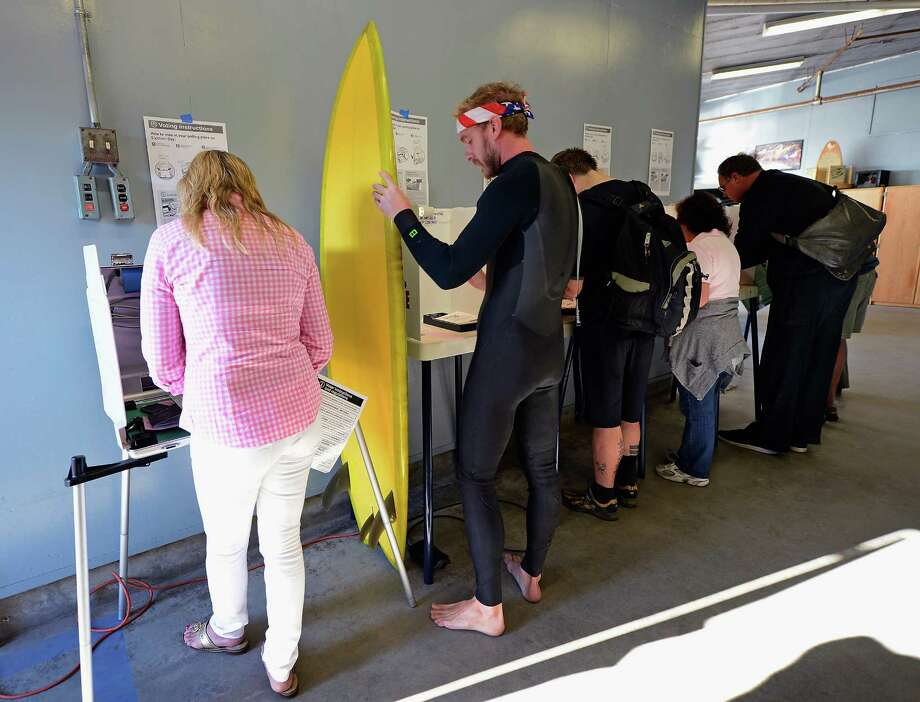 "Mike Wigart (2nd L), 30, secures his surfboard against a ballot box during U.S. presidential elections at a polling station in the garage of the Los Angeles County lifeguard headquarters on November 6, 2012 in Los Angeles, California. Californians will cast ballots in dozens of tight races including Gov. Jerry Brown's tax plan, abolishing the death penalty, easing the state's strict ""three strikes"" sentencing law and also in the Presidential race between Democratic President Barack Obama and Republican candidate Mitt Romney. Photo: Kevork Djansezian, Getty Images / 2012 Getty Images"