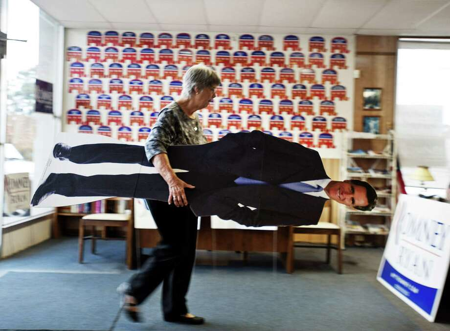 Volunteer Clare Frew puts away a life-size cut out of presidential hopeful Mitt Romney as she prepares to close the Chatham County Republican Campaign office, Tuesday, Nov. 6, 2012, in Savannah, Ga.  After a grinding presidential campaign, Americans are heading  into polling places across the country. Photo: Stephen Morton, Associated Press / FR56856 AP