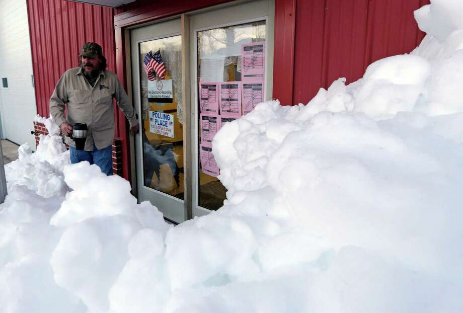 Snow surrounds the polling precinct in Terra Alta, W.Va., as Peter Hough heads to work after casting his ballot on Election Day, Tuesday, Nov. 6, 2012. Photo: Dave Martin, Associated Press / AP