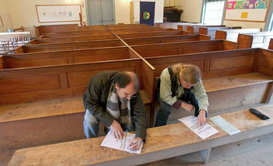 James Ventresca, left, and Claudia Welch fill out their ballots at Town Hall on Election Day, Tuesday, Nov. 6, 2012 in Calais, Vt. Photo: Toby Talbot, Associated Press / AP