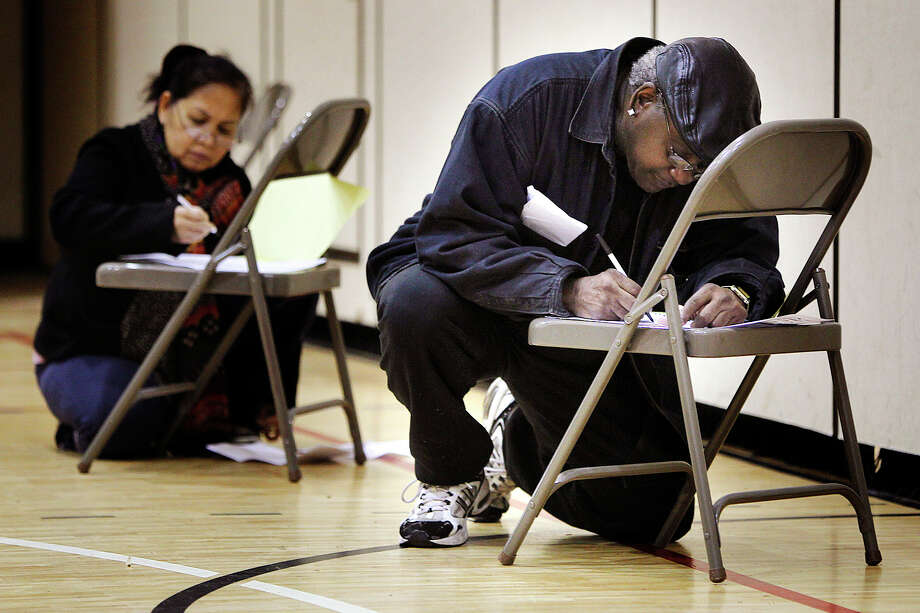 Donald Clark votes on a chair on the gym floor of the third ward precinct at Marcy School, Tuesday, Nov. 6, 2012, in Minneapolis. Photo: Elizabeth Flores, Associated Press / The Star Tribune