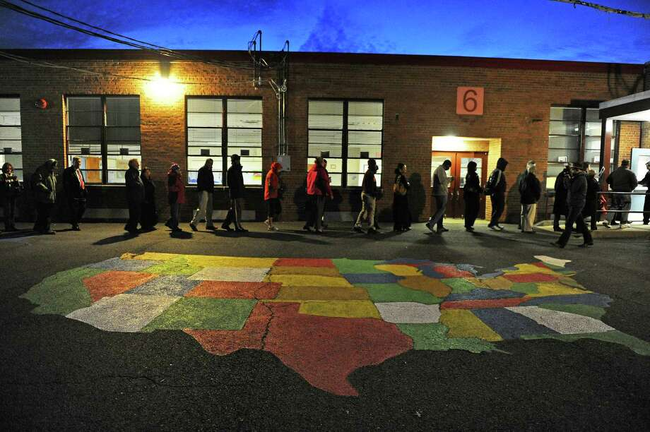 People enter Washington Mill Elementary School to cast their vote in the U.S. presidential race, on November 6, 2012, in Alexandria, Virginia. Recent polls show that U.S. President Barack Obama and Republican presidential candidate Mitt Romney are in a tight race. Photo: Patrick Smith, Getty Images / 2012 Getty Images