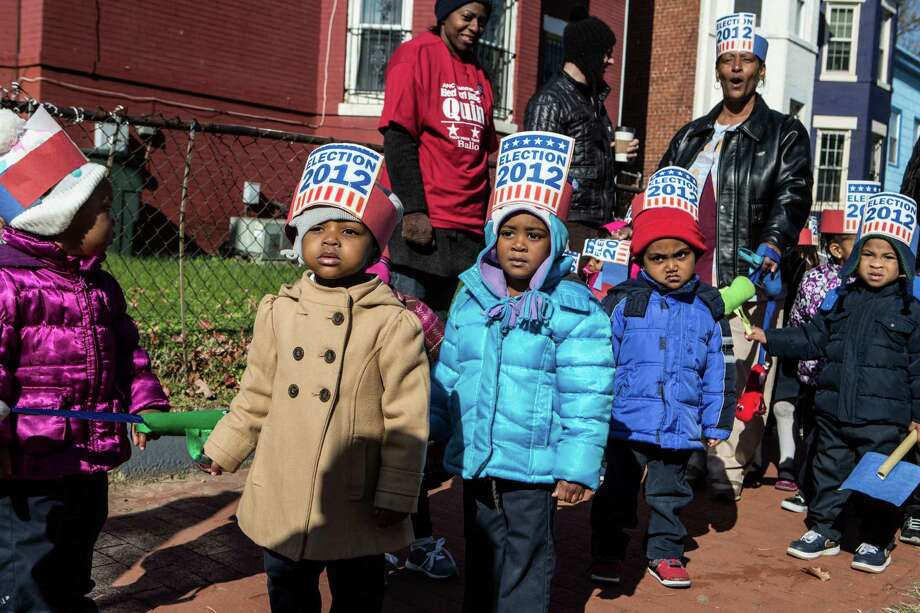 Children from Kingdom Kinds Child Development Center march past a polling station to get out the vote at Dunbar High School on November 6, 2012 in Washington, DC. The latest polls continue to show a tight race between President Barack Obama and Republican challenger Mitt Romney. Photo: Brendan Hoffman, Getty Images / 2012 Getty Images