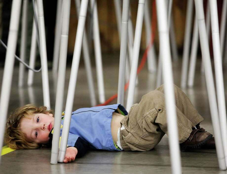 Two-year-old Ben Baskett stretches out under the voting booth while his mother, Sherry Pikul, votes, Tuesday, Nov. 6, 2012. Photo: Shawn Raecke, Associated Press / Livingston Enterprise