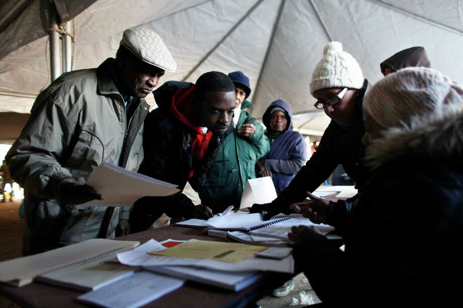 Voters check in before casting their ballots under a tent at a consolidated polling station for residents of the Rockaways on Election Day, Tuesday, Nov. 6, 2012, in the Queens borough of New York. Election Day turnout was heavy in several storm-ravaged areas in New York and New Jersey, with many voters expressing relief and even elation at being able to vote at all, considering the devastation. Photo: Jason DeCrow, Associated Press / FR103966 AP