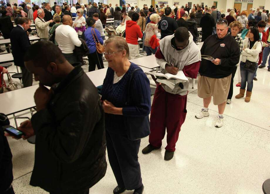 People wait in a long line at Greenbriar Middle School earl  Tuesday afternoon Nov. 6, 2012, In chesapeake, Va. Voters said it took them three hours or longer to cast their ballot. Photo: Brian Clark, Associated Press / The Virginian-Pilot