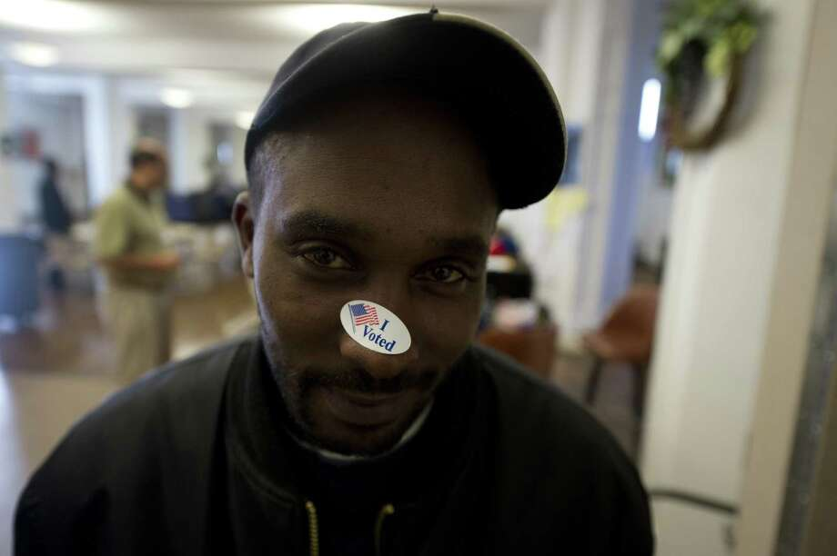 Brad Walker, 36, a first-time voter, puts his sticker on his nose after casting his ballot at St Patrick's Church polling station November 6, 2012 on the southside of Youngstown, Ohio.  Recent polls show U.S. President Barack Obama and Republican presidential candidate, former Massachusetts Gov. Mitt Romney locked in a tight race. Photo: Jeff Swensen, Getty Images / 2012 Getty Images