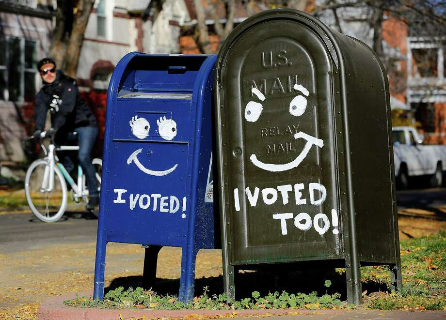 A biker passes by a pair of mailboxes in the Capitol Hill neighborhood November 6, 2012 in Denver, Colorado. Colorado is considered by most experts to be one of the key battleground state in this year's presidential election. Photo: Marc Piscotty, Getty Images / 2012 Getty Images