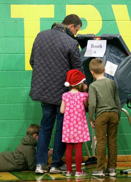 Peter Johnson, top left, casts his ballot with help from his three children Joe, 8, obscured bottom