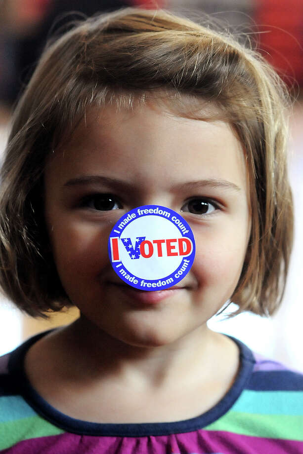 "Maria Moresea, 4, poses while wearing an ""I Voted"" sticker on her nose as she waits for her mother to finish voting at the Buckley precinct, Tuesday Nov. 6, 2012, in Fairview, Ky. Photo: Kevin Goldy, Associated Press / The Independent"