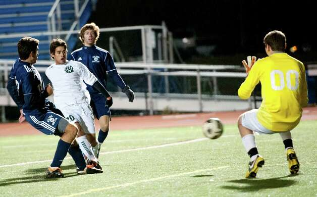 Norwalk high school's Nacho Navarro tries to get a shot by Wilton high school goalie Peter Como in the FCIAC boy's soccer semifinal game held at Fairfield Ludlowe high school, Fairfield, CT on Tuesday November 6th, 2012.Wilton goaliePeter Como  Photo: Mark Conrad / Stamford Advocate Freelance