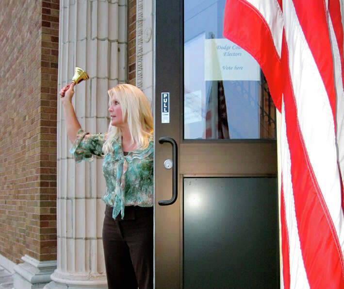 Waupun City Clerk Angie Hull rings a hand bell outside city hall, Tuesday, Nov. 6, 2012, to official