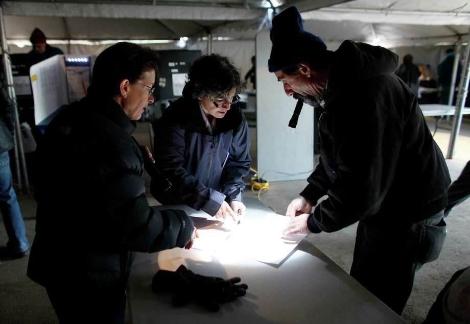 Election workers help a voter, right, finalize his affidavit ballot at a consolidated polling station for residents of the Rockaways on Election Day, Tuesday, Nov. 6, 2012, in the Queens borough of New York. Election Day turnout was heavy in several storm-ravaged areas in New York and New Jersey, with many voters expressing relief and even elation at being able to vote at all, considering the devastation. Photo: Jason DeCrow, Associated Press / FR103966 AP