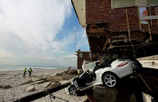 A badly damaged home is entangled with a vehicle along the beach in the Belle Harbor section of the Rockaway neighborhood of the borough of Queens, New York, Monday, Nov. 5, 2012, in the wake of Superstorm Sandy. Temperatures dipped toward freezing early Monday, and tens of thousands of people without power along the ravaged Atlantic coastline faced the prospect of finding somewhere else to stay. Photo: Craig Ruttle, Associated Press / FR61802 AP