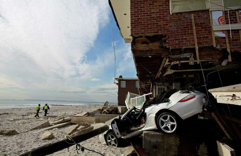 A badly damaged home is entangled with a vehicle along the beach in the Belle Harbor section of the